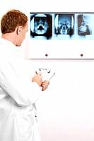Doctor writing on clipboard while looking at X_ray images