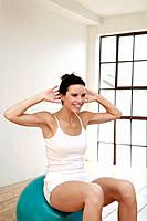 Woman sitting on fitness ball, exercising