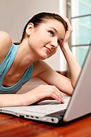 Woman lying forward on the floor using laptop