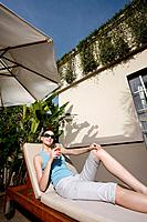 Woman with sunglasses relaxing on lounge chair with a glass of fruit juice