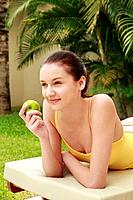 Woman lying forward on lounge chair holding green apple
