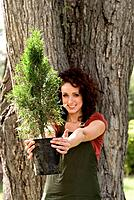 Woman stands beside large tree, holding smaller tree toward camera, Winnipeg, Manitoba, Canada