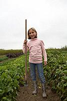 Young girl, 9 yrs, holding hoe in organic garden, Ladner, British Columbia, Canada