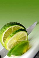 A knife cutting a lime