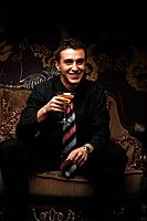 Businessman holding a cocktail while smiling at the camera