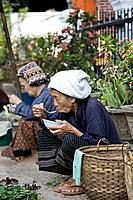 An old woman eating in a market in Asia,Laos