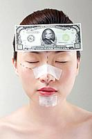 Woman with cosmetic surgery markings and banknote sticking her forehead