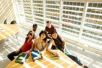 High angle portrait of students seated around table in front of solar panelled windows, Winnipeg, Canada