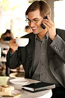 Businessman having a cup of coffee while talking on mobile phone