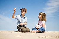Four year old girl and seven year old boy look at shells, Grand Beach Provincial Park, Manitoba, Canada