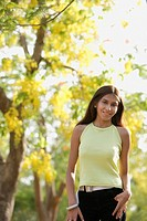 teen girl standing under blooming tree