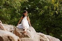 girl in white sari, sitting on rock