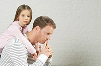 Girl embracing reflective father from behind