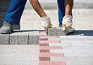 Construction worker setting paving stones