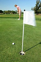 Golf flag in a hole with a woman in the background