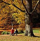 Two senior women on a bench in autumn