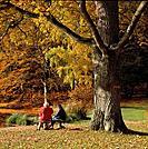 Two senior women on a bench in autumn
