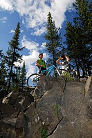 Pair of mountain bikers viewing the scene atop a cliff