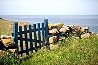 Blue fence and a stone wall at the sea