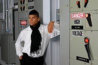 Man posing ominously beside large high voltage circuit breakers