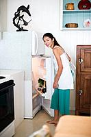 A young woman opening refrigerator