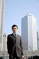 Businessman against office buildings, portrait