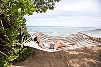 A woman lying on hammock at beach