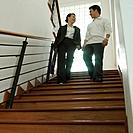 Low angle view of a businessman and a businesswoman talking to each other on a staircase
