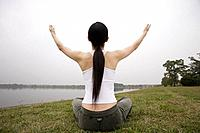 Rear view of a young woman in lotus position