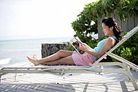 A woman reading book on deck chair