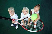 Kids playing with an oversized tennis racket and ball