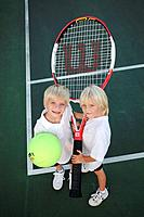 Kids with an oversized tennis racket and ball
