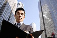 Businessman browsing a file, portrait