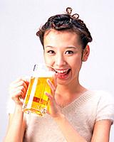 A Woman Drinking a Glass of Beer, Smiling, Looking at Camera, Front View