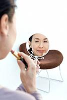 Closed Up Image of a Mature Adult Woman Putting on Makeup, Differential Focus, Rear View