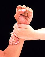 Woman gripping arm of man with fist