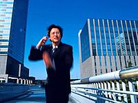 Businessman running and holding a mobile phone in the city, low angle view, blurred motion