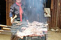 man cooking barbecue on spit