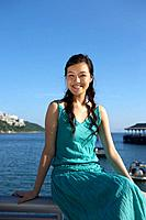 Young Lady Sitting on Railing of Fence, Smiling (thumbnail)