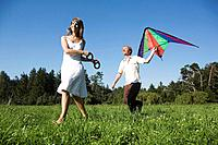 Germany, Bavaria, Young couple flying kites in meadow