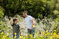 Germany, Baden Württemberg, Tübingen, Father and son 11 walking in meadow