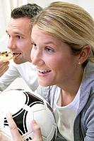 Young couple watching TV with football and pizza
