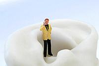 Business man figurine using mobile phone
