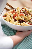 Woman holding dish of pasta salad with olives and tomatoes
