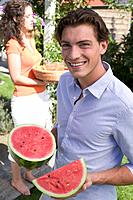 Young man holding watermelon, woman with iced tea in background