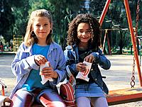 two girls eating popcorn in a park