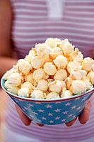Woman holding popcorn in bowl with stars 4th of July, USA