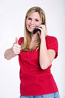 Young woman using mobile phone, thumbs up, portrait