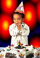 a black happy boy looking his birthday table