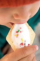 Child eating iced biscuit decorated with sprinkles